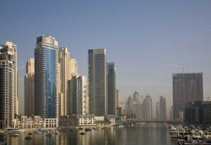 UAE, Dubai Marina towers with boats at anchor